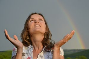Beautiful girl looking at sun sky after the rain with hands open in gratitude